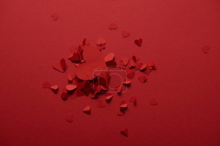 Photo for Top view of decorative paper cut hearts on red background - Royalty Free Image