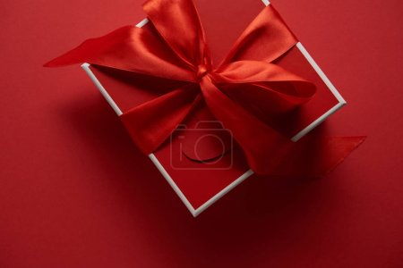 top view of red gift box with satin ribbon on red background