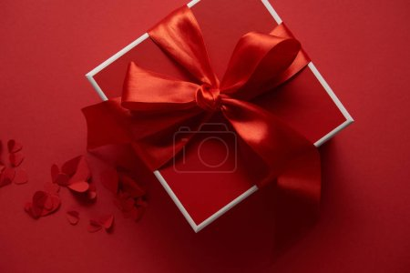 top view of red present with silk ribbon and paper cut hearts on red background