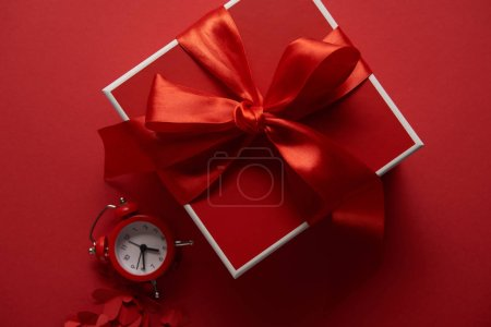 top view of red present with silk ribbon, clock and paper cut hearts on red background