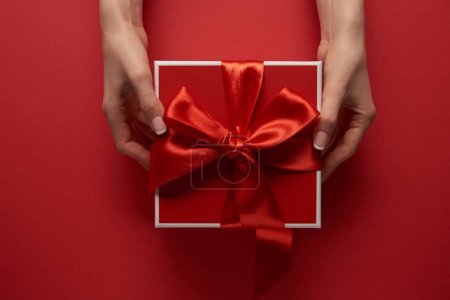 Photo for Partial view of female hands holding present with silk ribbon on red background - Royalty Free Image