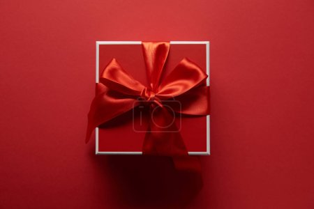 Photo for Top view of present with silk ribbon on red background - Royalty Free Image