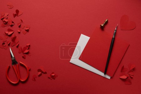 top view of paper cut hearts, scissors and empty greeting cards on red background