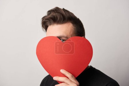 Photo for Man with obscure face holding empty paper cut heart card and looking at camera - Royalty Free Image