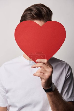 man with obscure face holding empty paper cut heart card isolated on grey
