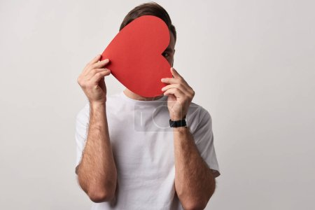 man hiding face behind empty red paper cut heart card isolated on grey
