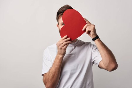 man hiding face behind blank paper cut heart card isolated on grey