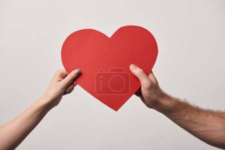partial view of couple holding together blank heart card isolated on grey