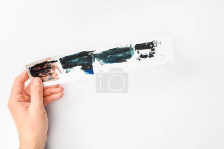 Foto de Hombre que sostiene el papel con pinceladas de acuarela abstractas en fondo blanco - Imagen libre de derechos