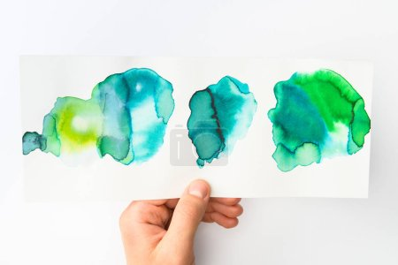 Man holding paper with abstract watercolor blue and green spills on white background