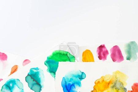Foto de Vista superior de los derrames de color de rosa, amarillos, verdes y azules acuarela abstractas sobre fondo blanco - Imagen libre de derechos