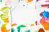 top view of frame with abstract watercolor spills on papers on white background