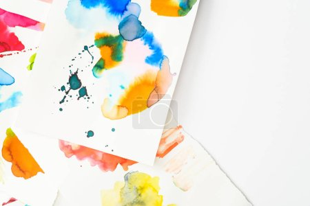 top view of papers with abstract watercolor spills on papers with copy space