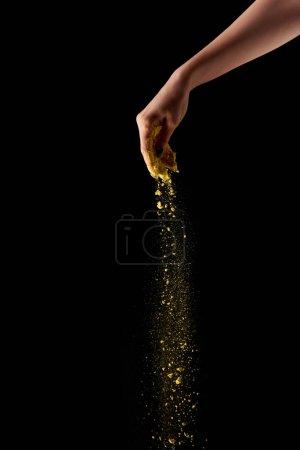 Photo pour Vue recadrée de la femme adulte saupoudrer de poudre holi jaune sur fond noir - image libre de droit