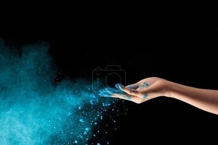 vista recortada de la mujer adulta con polvo de holi azul sobre fondo negro