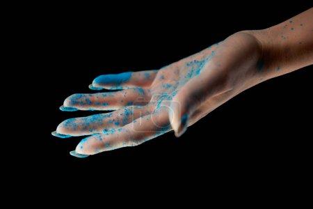 Photo pour Vue recadrée de la femme adulte avec poudre holi bleu isolé sur noir - image libre de droit