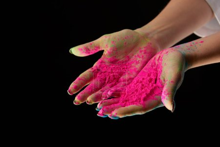 cropped view of adult woman with pink holi powder on hands isolated on black