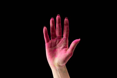 cropped view of adult woman showing pink holi powder on hand isolated on black