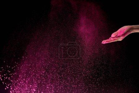 vista recortada de la mujer adulta con polvo de holi rosa en el aire sobre fondo negro