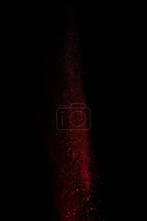 Photo for Red powder in air and falling down on black background - Royalty Free Image