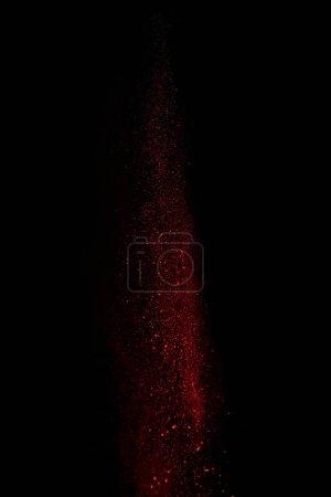 Photo pour Poudre rouge dans l'air et tombant sur fond noir - image libre de droit