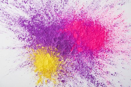 top view of explosion of purple, pink and yellow holi powder on white background