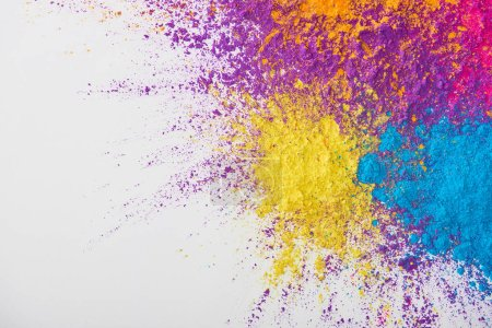 top view of explosion of yellow, purple, orange and blue holi powder on white background