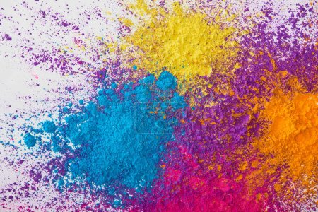 top view of explotion of yellow, purple, orange and blue holi powder on white background