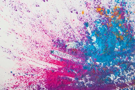 Foto de Vista superior de explosión de polvo de holi púrpura y azul sobre fondo blanco - Imagen libre de derechos