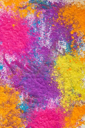 top view of explosion of multicolored holi powder on white background