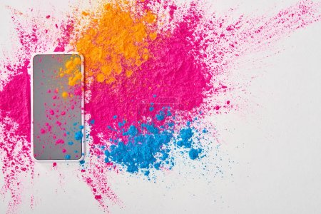 Photo for Top view of smartphone and explosion of multicolored holi powder on white background - Royalty Free Image