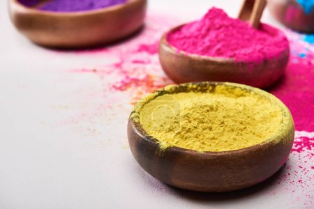selective focus of wooden bowls with yellow, pink, blue and purple holi powder on white background