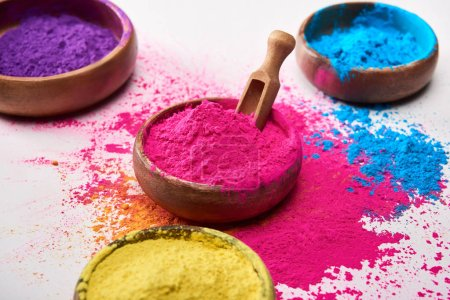 wooden spatula and bowls with yellow, pink, blue and purple holi powder on white background