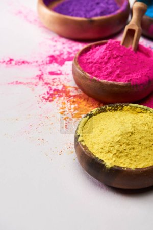 wooden bowls with pink and yellow holi powder on white background