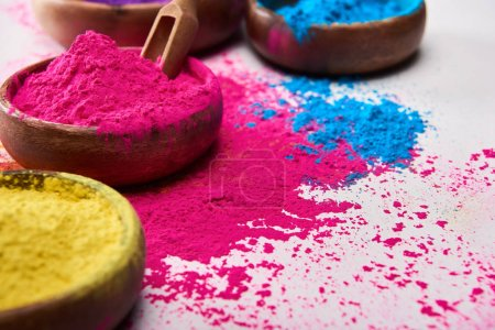 wooden spatula and bowls with pink, blue and yellow holi powder on white background