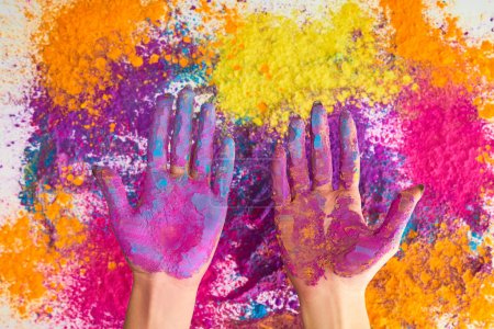 cropped view of woman showing hands in multicolored holi powder