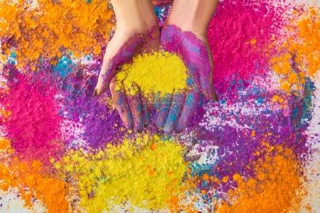 vista recortada de la mujer y polvo de holi multicolor