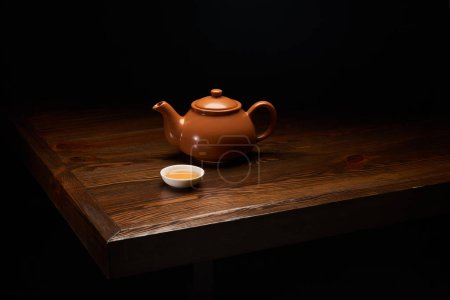 pot with traditional chinese tea and cup on wooden table isolated on black