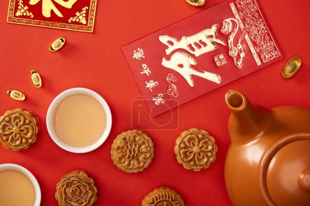 top view of traditional mooncakes with chinese hieroglyphs and tea isolated on red
