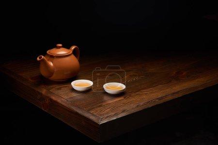 Photo pour Pot à thé chinois traditionnel et les barquettes sur une table en bois isolé sur fond noir - image libre de droit