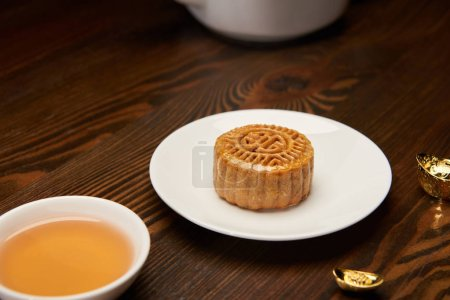 selective focus of mooncake with tea cup and gold ingots on wooden table