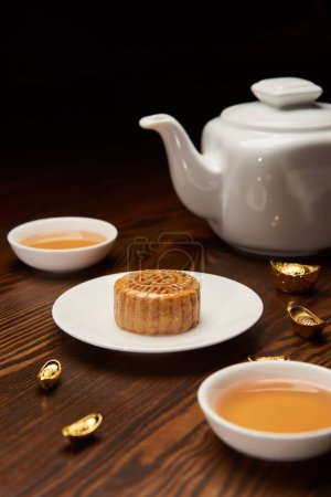 traditional mooncake with tea cups, pot and gold ingots isolated on black
