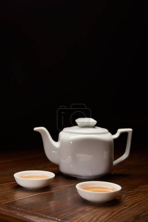 tea pot and cups with traditional chinese tea isolated on black with copy space