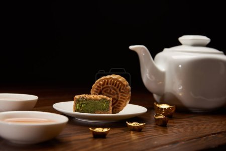 traditional delicious chinese mooncakes, tea pot and gold ingots on wooden table isolated on black