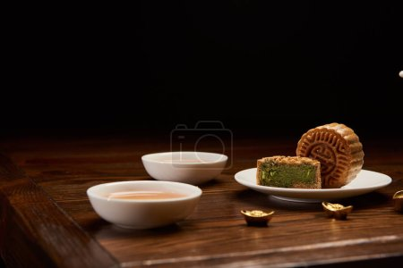 traditional chinese mooncakes, cups of tea and gold ingots isolated on black