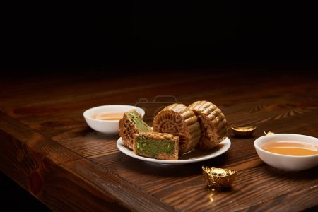 Photo for Traditional chinese mooncakes, cups of tea and gold ingots isolated on black - Royalty Free Image