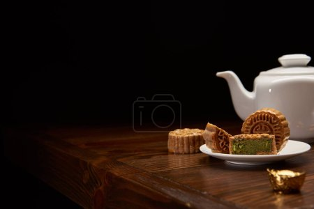 traditional chinese mooncakes, tea pot and gold ingot on wooden table isolated on black with copy space