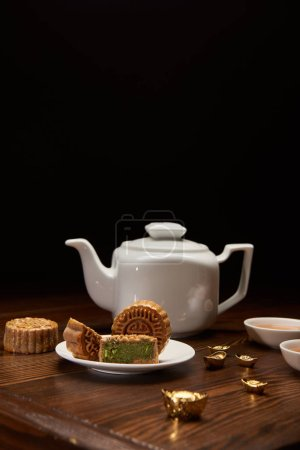 Photo for Traditional chinese mooncakes, tea pot and gold ingots on wooden table isolated on black - Royalty Free Image