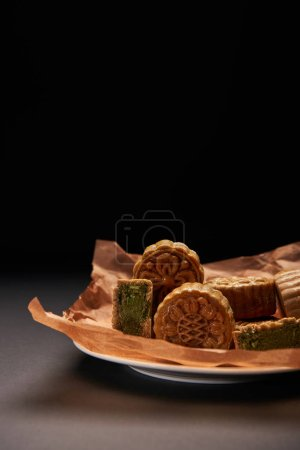 Photo for Traditional chinese mooncakes on plate isolated on black with copy space - Royalty Free Image