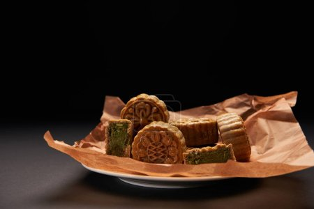 traditional chinese mooncakes on plate isolated on black with copy space